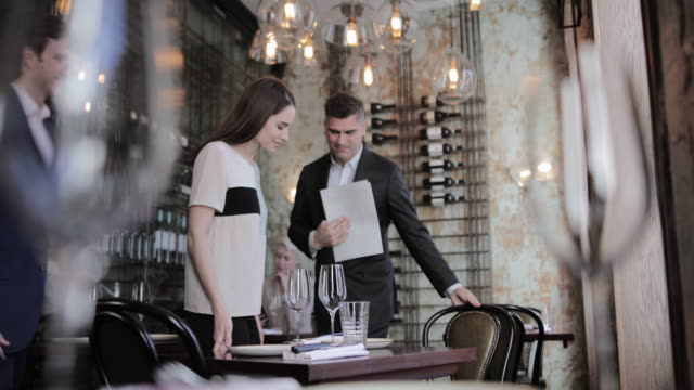 waiter seating couple in a restaurant - seat stock videos & royalty-free footage