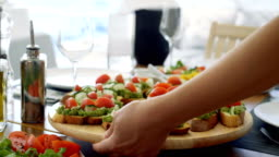 Waiter Serves Beautiful Organic Avocado Sandwiches/ Bruschetta on a Wooden Tray, Table Furnished in Mediterranean Food: Seasonal Vegetables, Olive Oil.