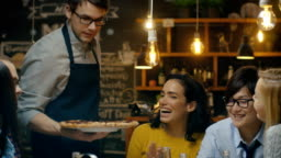 Waiter Serves Delicious Pizza to a Diverse Group Of Hungry and Happy Friends. They Eat, Drink and Have Fun in this Stylish Looking Bar.