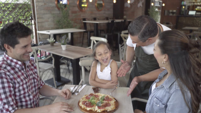 Waiter serving a pizza to a beautiful family at a restaurant