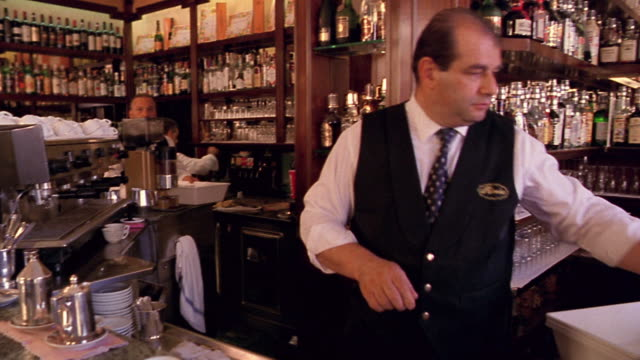 stockvideo's en b-roll-footage met waiter serving coffee + talking to someone offscreen at counter / florence, italy - koffie drank