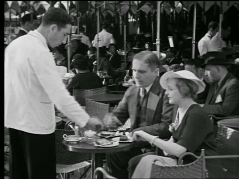 stockvideo's en b-roll-footage met b/w 1927 ms waiter serving couple at table in sidewalk cafe / other customers in background / paris, france - 1927