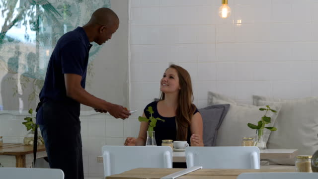 Waiter serving croissant to woman in coffee shop