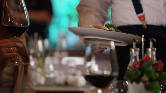 waiter serving dish 4k slow motion - ristorante video stock e b–roll