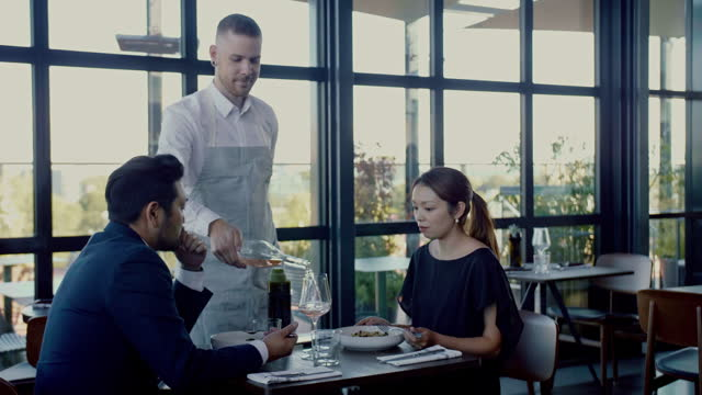 waiter serving drinks for japanese couple on a romantic date - catering building stock videos & royalty-free footage