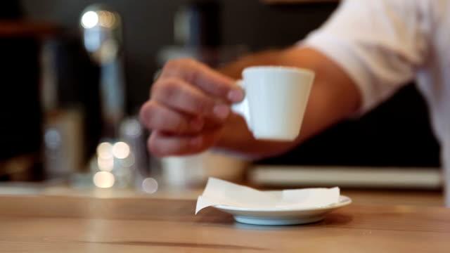 Waiter serving espresso at the bar