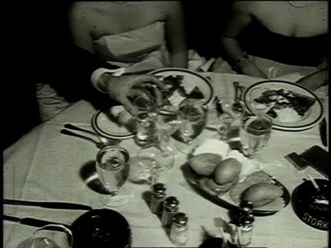 1962 MONTAGE waiter serving food and champagne to a group at a table / United States