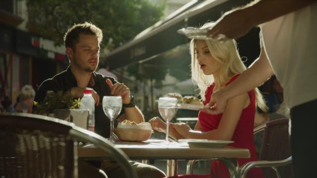 waiter serving food to couple at sidewalk cafe / seville, sevilla, spain - servitör bildbanksvideor och videomaterial från bakom kulisserna