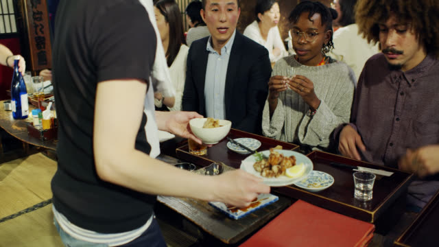 waiter serving food to customers in tokyo restaurant - tatami mat stock videos and b-roll footage