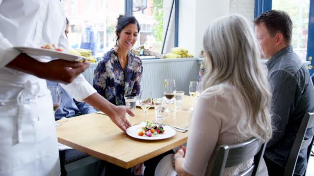 vídeos de stock, filmes e b-roll de ms tu pan waiter serving food to group of friends dining together in restaurant - garçom
