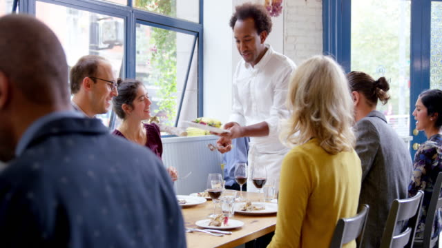 MS R/F waiter serving food to group of friends dining together in restaurant
