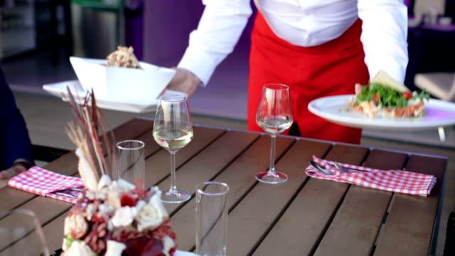 Waiter serving meal int restauran