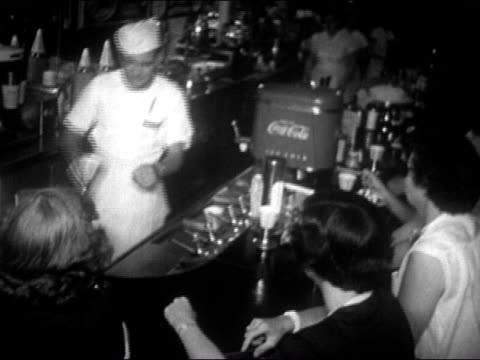waiter serving sundae to teenagers at soda fountain / usa / audio - サンデー点の映像素材/bロール