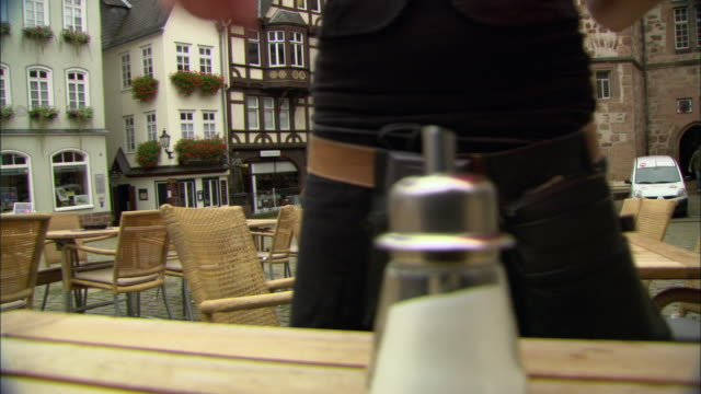 MS Waiter setting table in outdoor restaurant / Marburg, Germany