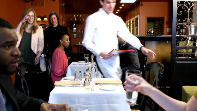 Waiter Shows Couple to Table at Busy Restaurant