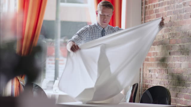 Waiter spreads tablecloth in restaurant dining room