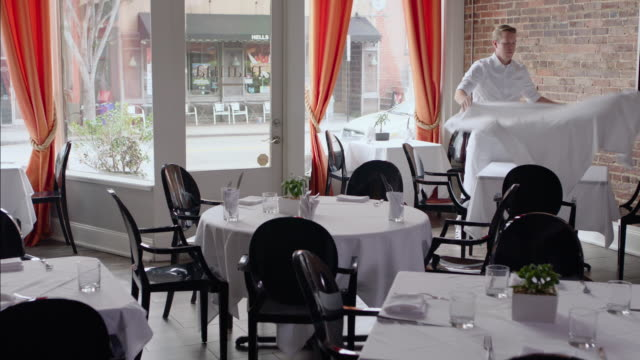 waiter spreads tablecloth in restaurant dining room - gourmet stock videos & royalty-free footage