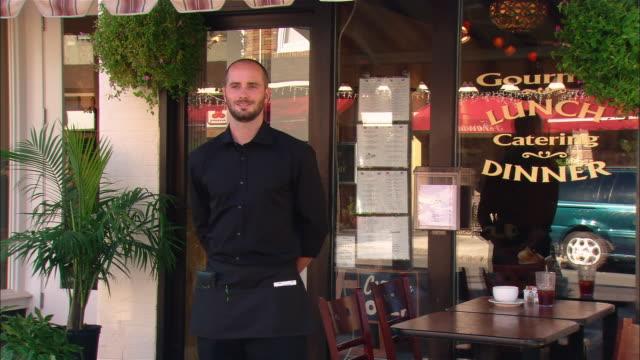 vidéos et rushes de waiter standing by sidewalk table in front of restaurant - devant