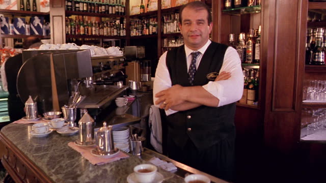 portrait waiter standing with arms crossed behind counter in cafe / florence, italy - cafe stock videos & royalty-free footage