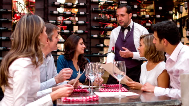 Waiter suggesting a wine to a group of people