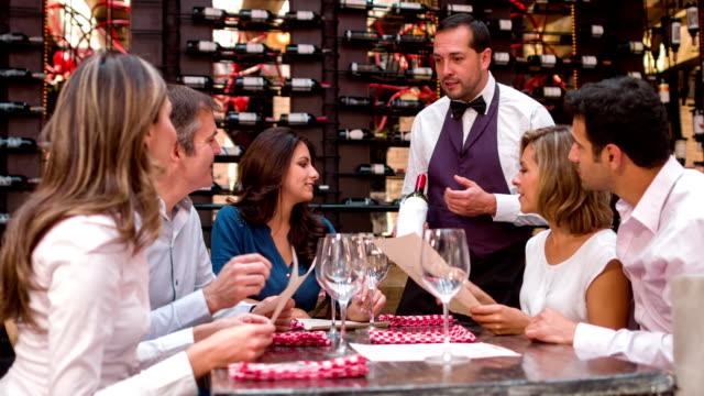 vídeos de stock e filmes b-roll de empregado de mesa, sugerindo um vinho para um grupo de pessoas - servir comida e bebida