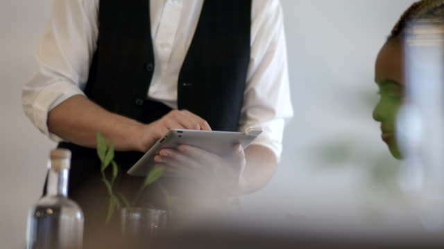 CU Waiter swipes customer card on digital tablet and hands device to woman to sign