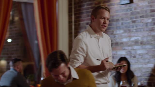 vídeos de stock e filmes b-roll de waiter takes dinner orders and jots them on notepad - jantar refeições