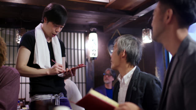 Waiter taking an order in a Japanese style restaurant