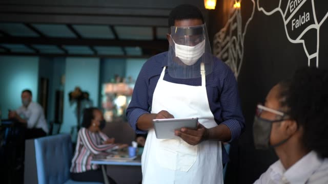 waiter taking client's order, using a digital tablet in a restaurant - using face mask - health and safety stock videos & royalty-free footage