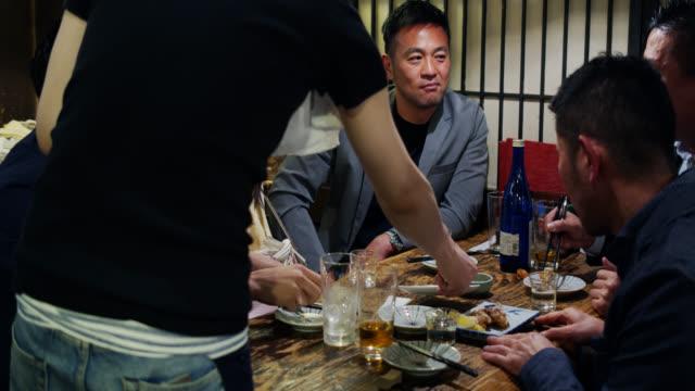 混雑した和食レストランのテーブルに食べ物を取っているウェイター - 居酒屋点の映像素材/bロール