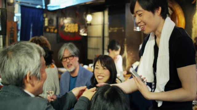混雑したレストランでモバイルクレジットカードの支払いを取るウェイター - 居酒屋点の映像素材/bロール