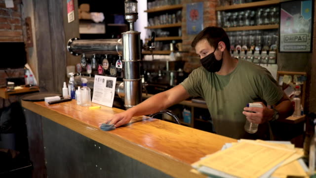waiter using disinfection product to clean bar counter before he open brewery - bar area stock videos & royalty-free footage