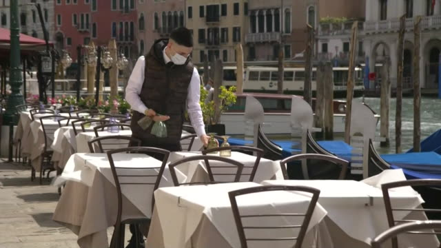 a waiter wearing a mask sets up tables at an outdoor restaurant in venice italy during the coronavirus pandemic - (war or terrorism or election or government or illness or news event or speech or politics or politician or conflict or military or extreme weather or business or economy) and not usa video stock e b–roll