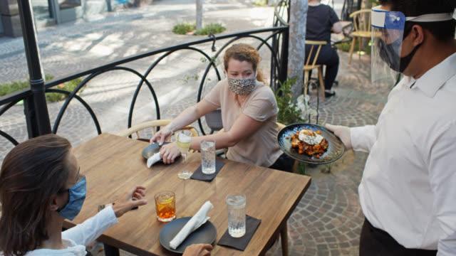 vídeos de stock e filmes b-roll de waiter wearing ppe during covid-19 pandemic bringing appetizer to masked customers - servir comida e bebida