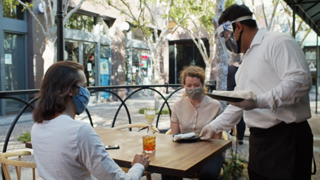 waiter wearing ppe during covid-19 pandemic bringing cutlery to customers at outdoor table - dining stock videos & royalty-free footage