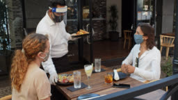 Waiter Wearing PPE During Covid-19 Pandemic Bringing Food to Customers on Patio