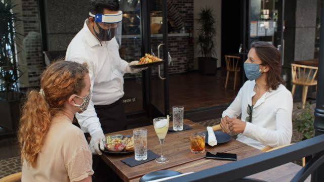 waiter wearing ppe during covid-19 pandemic bringing food to customers on patio - patio stock videos & royalty-free footage