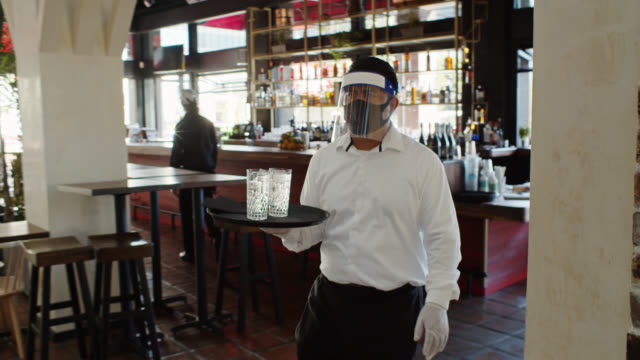 Waiter Wearing PPE During Covid-19 Pandemic Carrying Tray with Glasses of Water