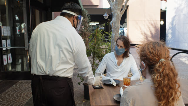Waiter Wearing PPE During Covid-19 Pandemic Serving Masked Customers at Outdoor Table