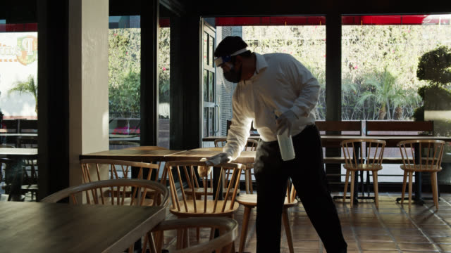 vídeos de stock e filmes b-roll de waiter wearing ppe during covid-19 pandemic wiping down tables - empregado de mesa