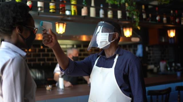 cameriere che indossa una maschera protettiva per il viso e misura la temperatura dei clienti - regole video stock e b–roll
