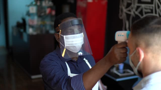 waiter wearing protective face mask and measuring temperature of customers - latin american and hispanic ethnicity stock videos & royalty-free footage
