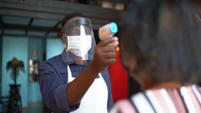 vídeos de stock, filmes e b-roll de garçom usando máscara facial protetora e medindo temperatura dos clientes - proteção