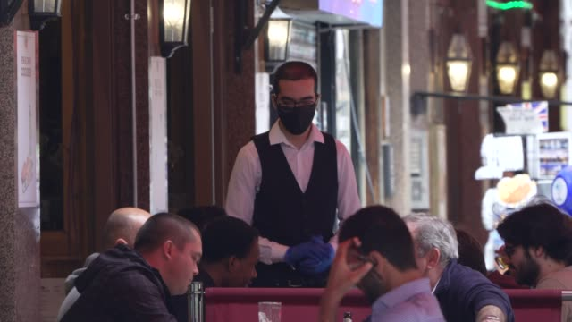 waiter wears a facemark as he serves customers on july 04, 2020 in london, england. the uk government announced that pubs, hotels and restaurants can... - uk stock videos & royalty-free footage