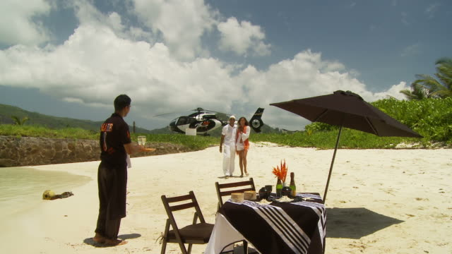 ws waiter welcoming arriving couple with champagne at table on sandy beach, helicopter on helipad in background / seychelles - pampering stock videos & royalty-free footage