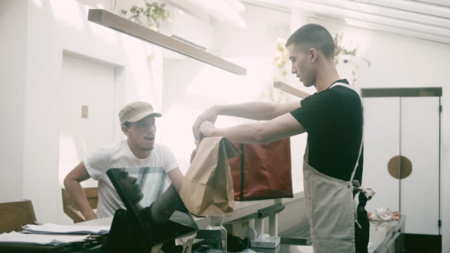 waiter wraps ordered food to the paper bag - paper bag stock videos & royalty-free footage
