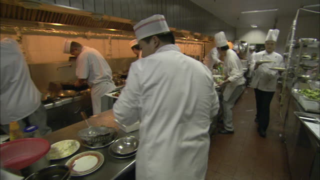 Waiters carry plates of food from a busy restaurant kitchen.