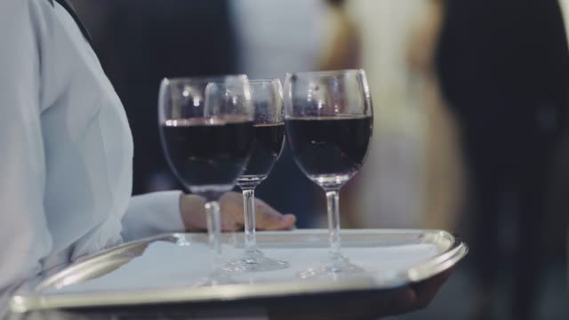 Waiters holds trays with glasses wine on reception