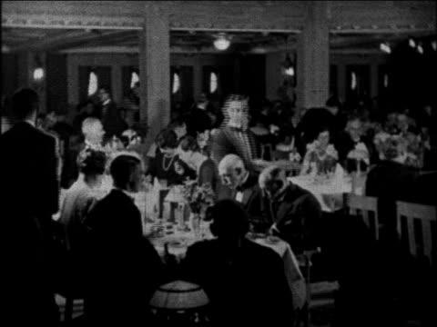 B/W 1930 waiters serving passengers eating in dining room of ocean liner / educational