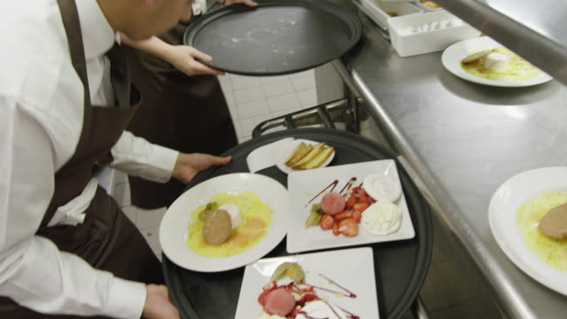 POV waiters taking prepared plates from the plating area in a restaurant kitchen to carry them to the dining room; camera follows waiter